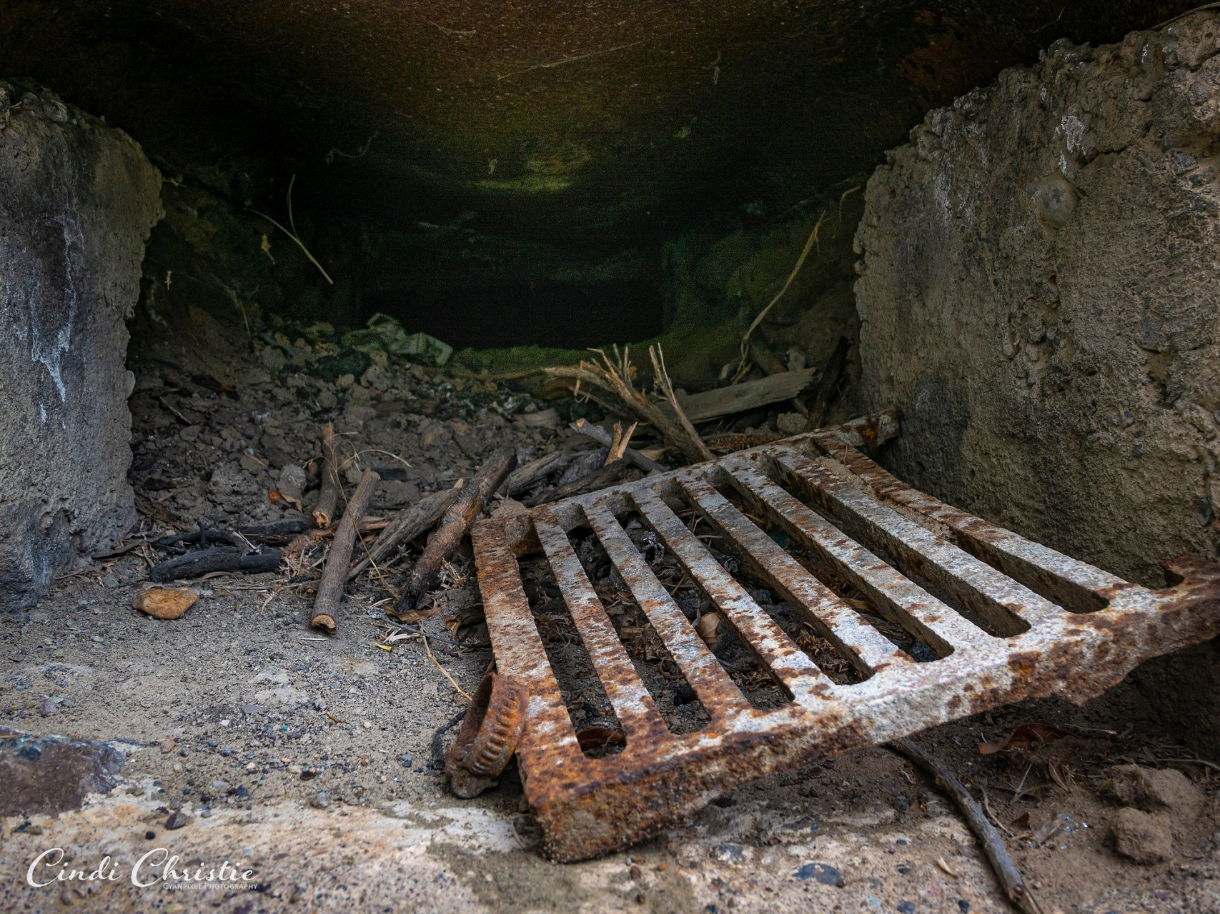 A well-used grate rests in an alcove in the wall.