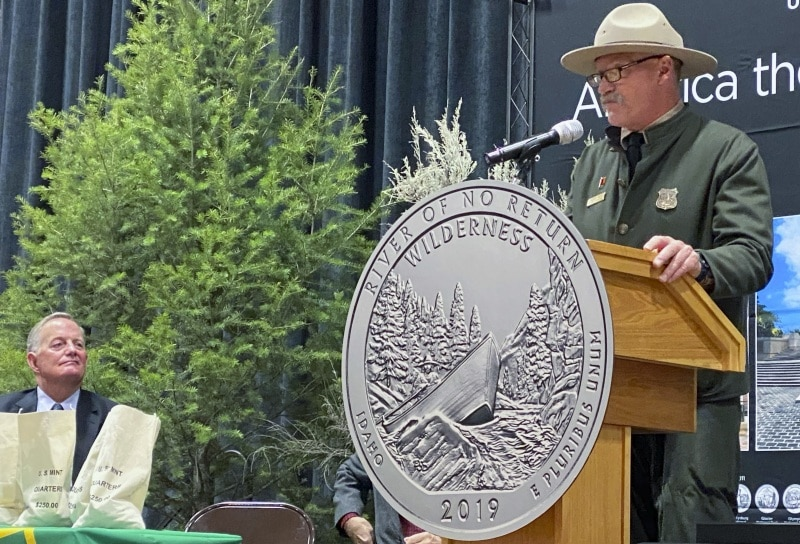 Garbed in a replica 1910 uniform, Charles Mark, Salmon-Challis National Forest supervisor, speaks as the Frank Church River of No Return Wilderness quarter is released on Wednesday, Nov. 6, 2019, during a ceremony at Salmon Junior-Senior High School in Salmon, Idaho. David Ryder, director of the U.S Mint, is seated behind currency bags at left, The coin is the 50th in the U.S. Mint's America the Beautiful series of quarters. (© 2019 Cindi Christie/Cyanpixel)