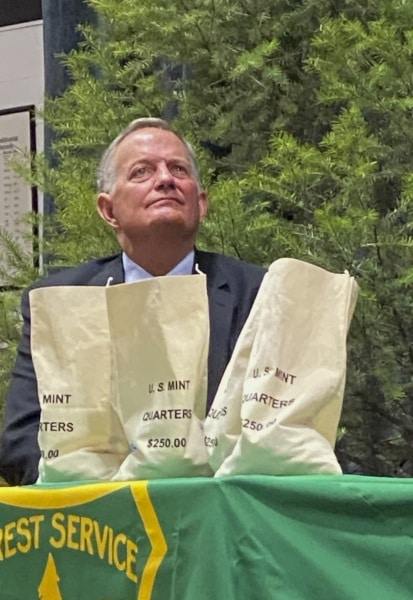 David Ryder, director of the U.S Mint, is seated behind currency bags as the Frank Church River of No Return Wilderness quarter is released on Wednesday, Nov. 6, 2019, during a ceremony at Salmon Junior-Senior High School in Salmon, Idaho. The coin is the 50th in the U.S. Mint's America the Beautiful series of quarters. (© 2019 Cindi Christie/Cyanpixel)